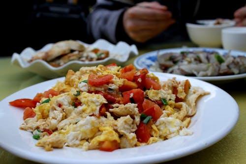 Çin usulü kızarmış domates yumurtası beyaz tabakta servis edilir ve başka bir tabakta kızarmış patlıcan