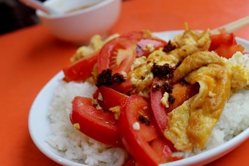 Çin usulü kızarmış domates ve yumurtalı omlet beyaz tabakta sıcak beyaz pirinç üzerinde servis edilir.