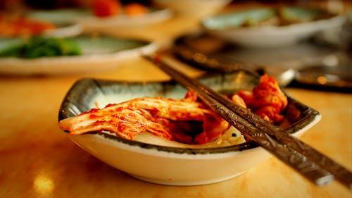Üstüne metal gümüş çubuklar yerleştirilmiş beyaz bir kapta kimchi