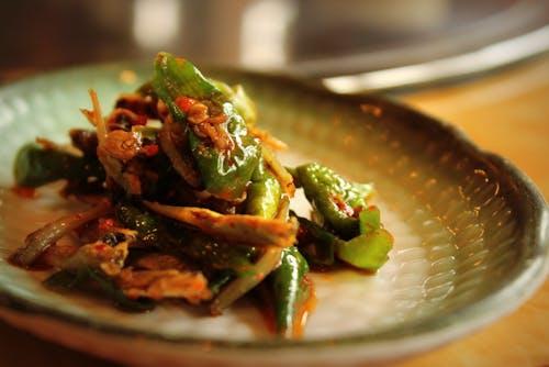 Beyaz tabakta fermente yeşil biberli Kore usulü kimchi.