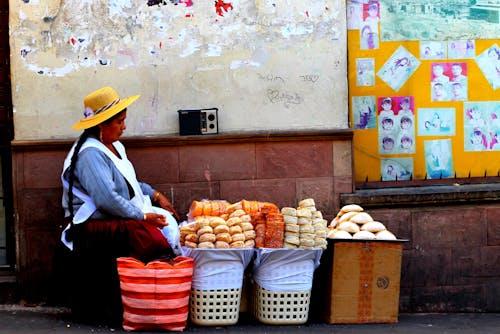 Bolivya'da taş duvara karşı tatlı şeker yığınları satan güneş şapkası takan Bolivyalı kadın