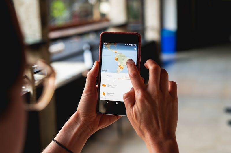 Cep telefonunda haritada gezinmek için parmağını kullanan kız