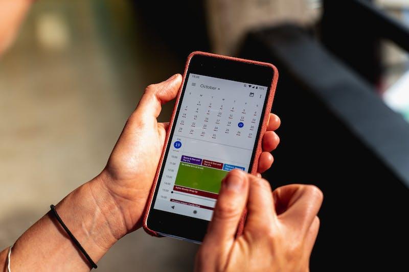 Google Takvim arayüzüne bakan kırmızı kılıflı bir Google Pixel telefonu tutan bir kızın elleri