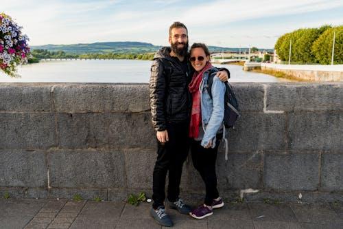Limerick İrlanda'da bir nehir üzerinde bir taş köprüde gülümseyen güneş gözlüğü takan sakallı adam ve kadın