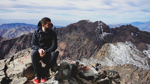 Atlas Dağları'ndaki Toubkal Dağı'nın zirvesinde bir kayanın üzerinde oturan siyah ceketli adam