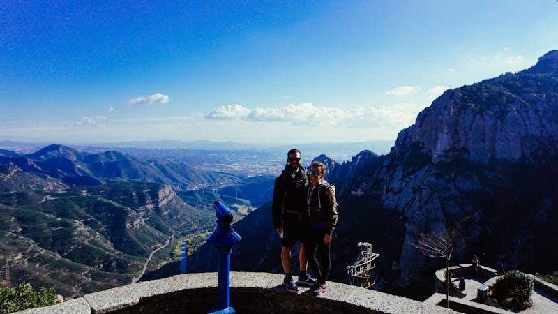 Montserrate'de mavi gökyüzü, kabarık beyaz bulutlar ve uzaktaki mavi dağlarla bir fotoğraf için poz veren kadın ve erkek