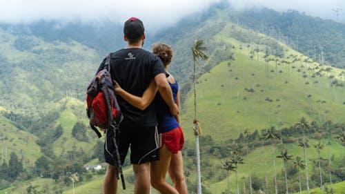 Siyah gömlekli adam ve kırmızı şortlu kız, palmiye ağaçlarıyla dolu yeşil tepelerde kollarını birbirine dolamış.