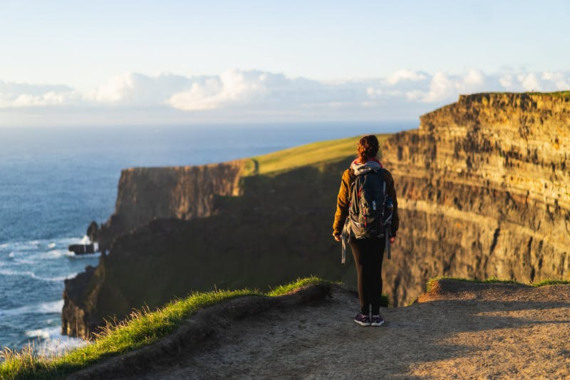 Moher İrlanda Kayalıkları'nda mesafeye bakan sırt çantası takan kız