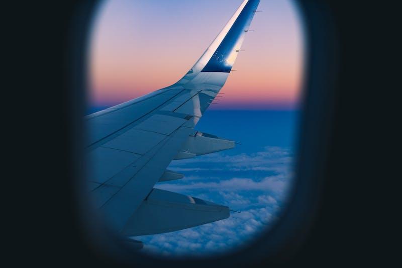 Bir uçak penceresi tarafından çerçevelenmiş pembe ve mor bir gün batımına karşı bir uçağın kanadı