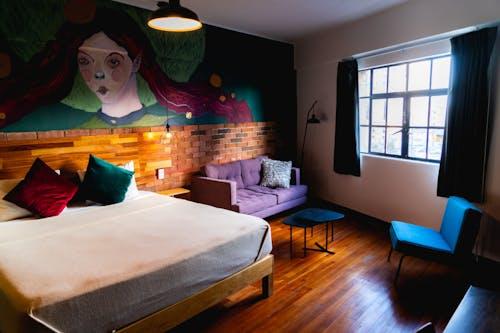 Kral yatak, duvar sanatı, mor kanepe ve mavi sandalye ile son moda bin yıllık tarzı hostel stüdyo daire