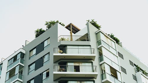 Bir apartmanda köşe balkonları ve çatı ağaçları