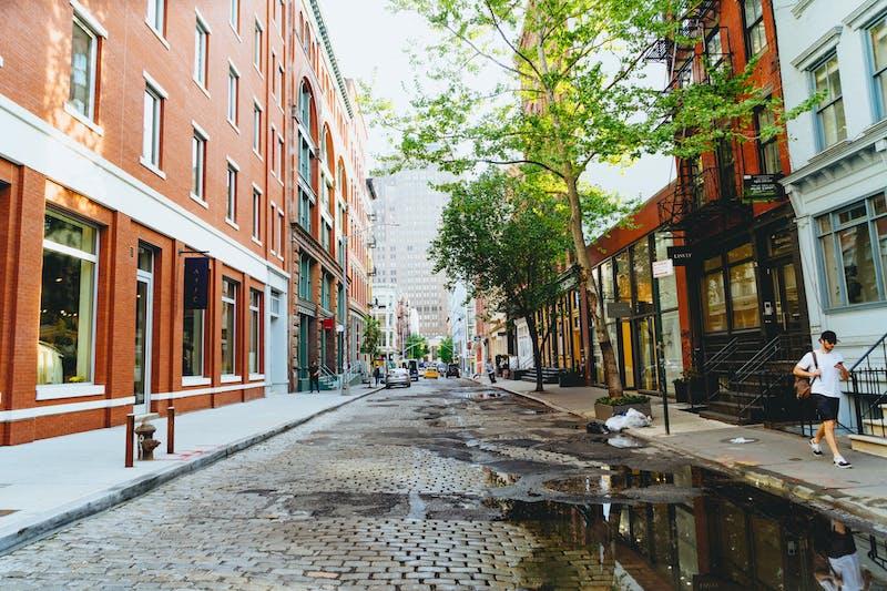Yaz yağmurundan sonra su birikintileri olan Arnavut kaldırımlı tarihi NYC caddesi