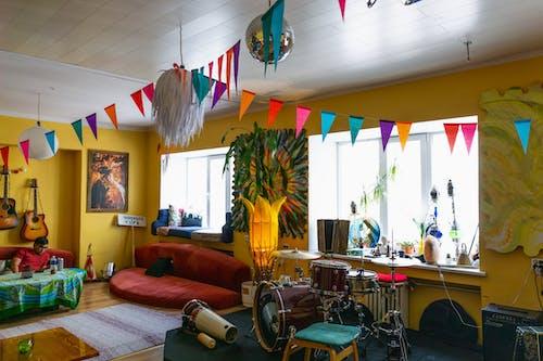 Sarı duvarlar ve duvarlarda gitarlar asılı bir hostel ortak alanında afiş bayrakları ve çok renkli mobilyalar