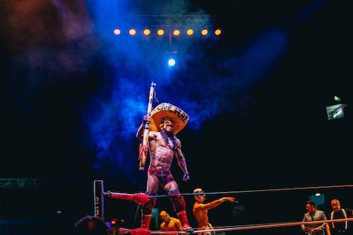 Mexico City'deki dövüş ringinde büyük fötr şapkalı Lucha Libre savaşçısı