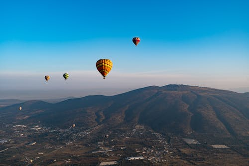 Açık mavi gökyüzüne karşı köylerin ve dağların üzerinde yüzen sıcak hava balonları