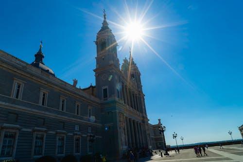 Madrid'deki büyük bir taş plazada ünlü bir kilisenin üzerinde güneş parlaması