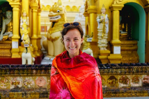 Altın Budist tarzı tasarımların önünde kırmızı ve turuncu bir Malaya peştemâli giyen kız