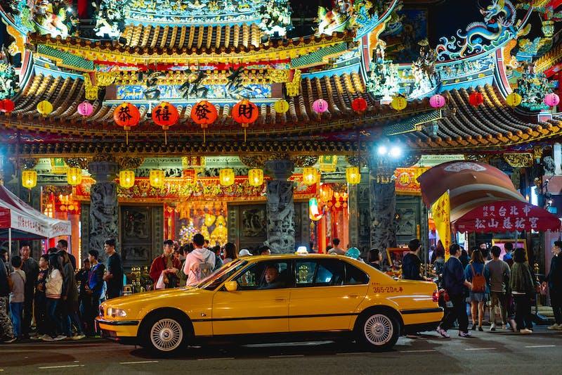 Önünde sarı bir taksi olan aydınlatılmış bir Budist tapınağının önünde asılı Çin sembolleri olan kırmızı fenerler