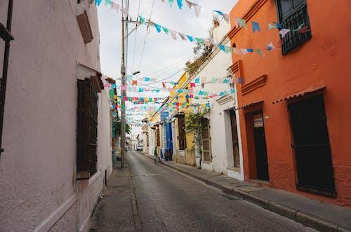 Küçük, çok renkli bayraklar, beyaz ve turuncu binaların olduğu küçük, sessiz bir caddede asılı duruyor.