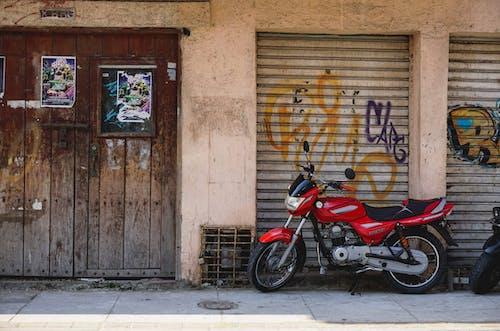 Ahşap bir dizi kapı, kapalı mağaza ızgaraları ve kırmızı ve siyah bir motosiklet