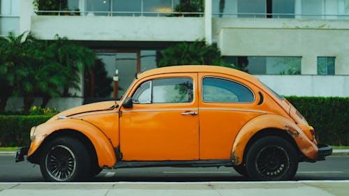 Beyaz bir apartmanın önünde sokakta park edilmiş Vintage Orange Volkswagen Beetle