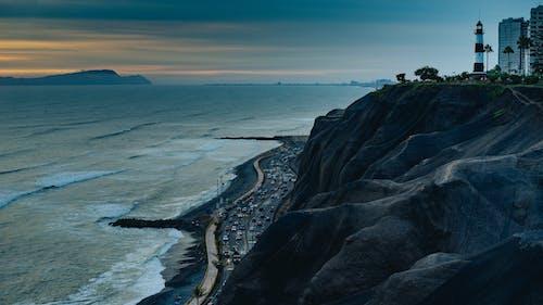Siyah beyaz bir deniz feneri ve binaları olan siyah sahil kayalıklarında kasvetli gün batımı