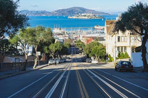 Alcatraz'ın net manzarasına sahip San Francisco'da boş bir yolda yokuş aşağı tramvay izleri