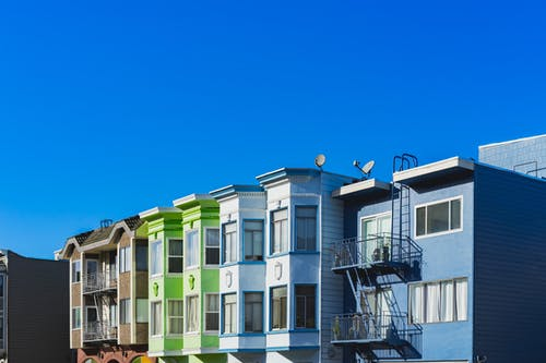 San Francisco'da açık mavi gökyüzüne karşı gökkuşağı renkli sıra evler