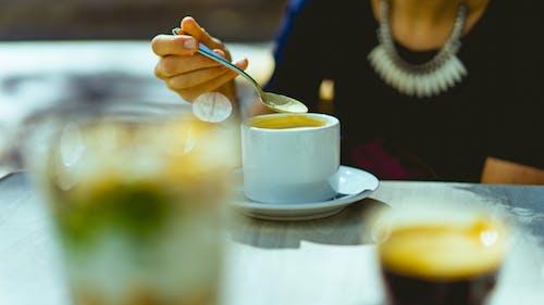 Siyah giyen kadın elinde bir kaşıkla kahveyi beyaz bir fincanda karıştırıyor.