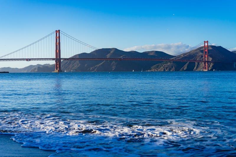 Golden Gate Köprüsü arka planda dağlar ve ön planda deniz köpüğü ile açık bir günde