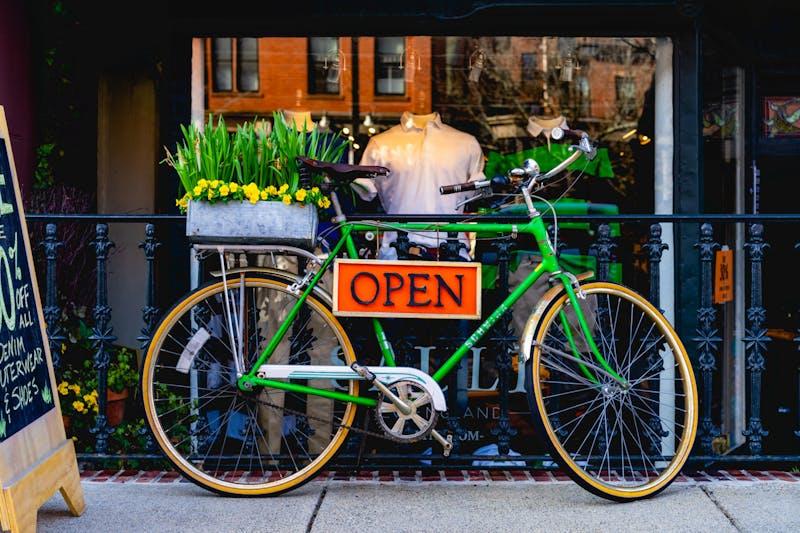 Turuncu AÇIK tabelası Boston'daki bir çiçekçi dükkanının önünde yeşil bir yol bisikletinde asılıydı.