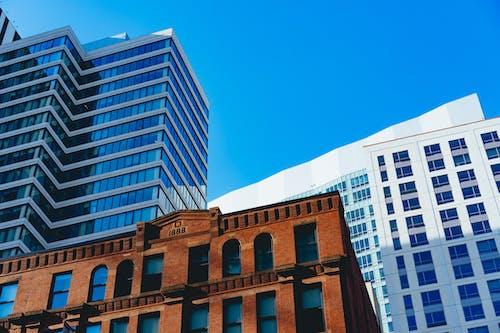 Boston'da mavi bir gökyüzüne karşı yeni gökdelenler ve eski endüstriyel kırmızı tuğla bina