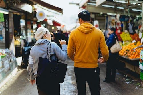 Tel Aviv'in merkezinde Shuk HaCarmel'de yürüyen kadın ve erkek