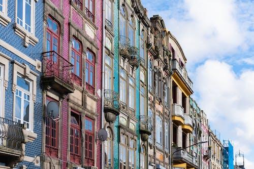 Yüksek pencereleri ve parçalı bulutlu mavi gökyüzü olan mavi, pembe ve turkuaz dar binalar