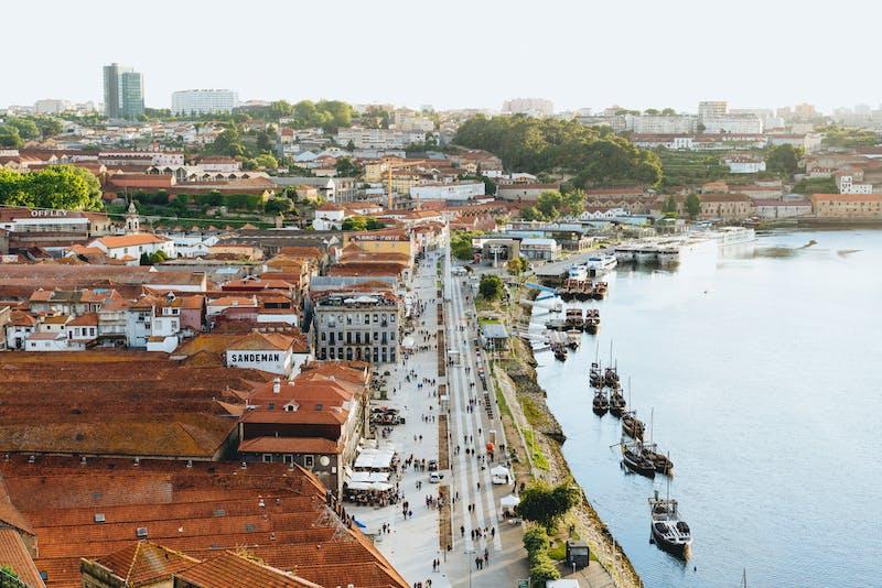 Kırmızı çatılı beyaz binalar ve teknelerle dolu bir nehrin yanında insanlarla dolu bir yaya geçidi