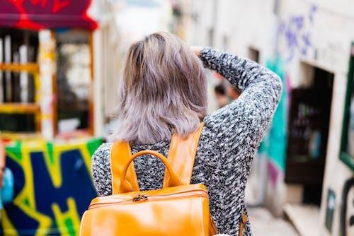 Mor saçlı ve parlak turuncu sırt çantası olan bir kız fotoğraf çekiyor.