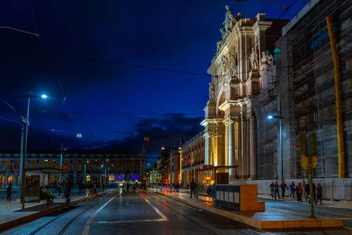 Lizbon'da parlak bir şekilde aydınlatılmış tarihi bir binanın yanındaki boş bir sokağın gece görünümü