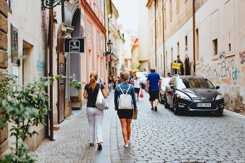 Pembe ve bej duvarlardan oluşan Arnavut kaldırımlı dar bir sokakta yürüyen kadınlar