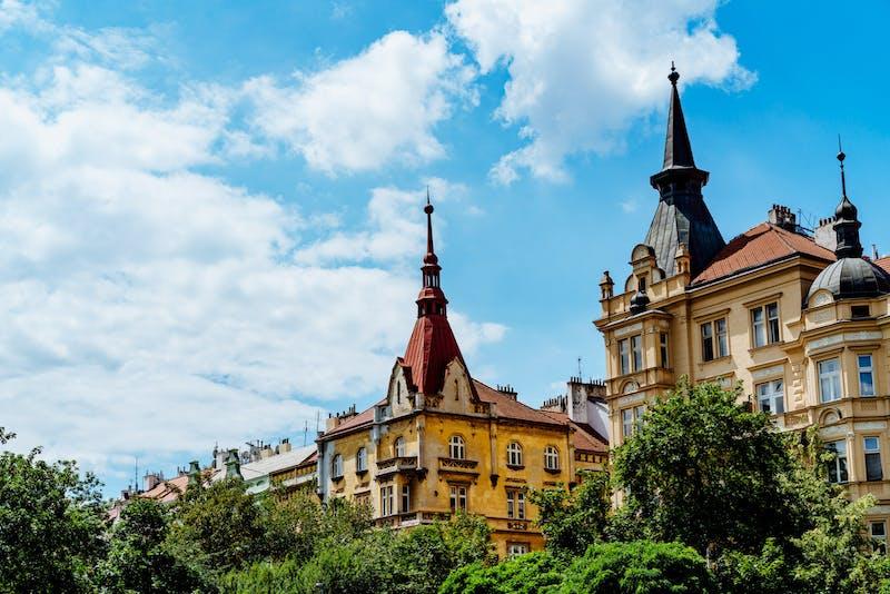 Uzun kırmızı ve siyah kuleleri olan sarı ve bej loncaların yanındaki yeşil ağaçlar