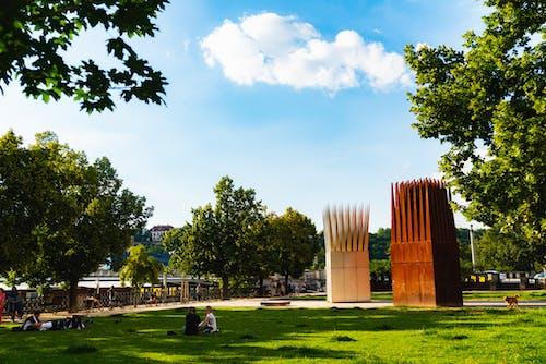 Çimenli bir parkta yeşil ağaçlar ve sivri uçlu kırmızı bronz heykeller