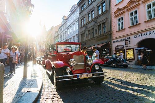 Bir güneş parlaması ile bir Arnavut kaldırımlı sokakta park edilmiş eski 1940'larda kırmızı araba