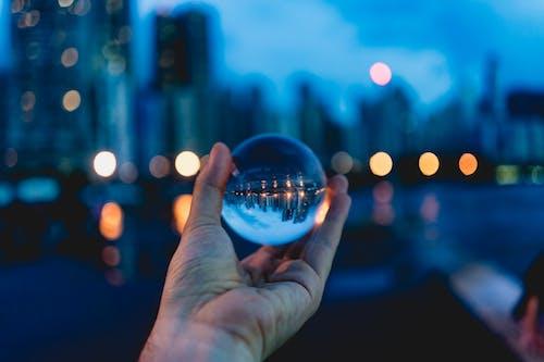 Cam bir kürede gökdelenlerin ve şehir ışıklarının yansıması