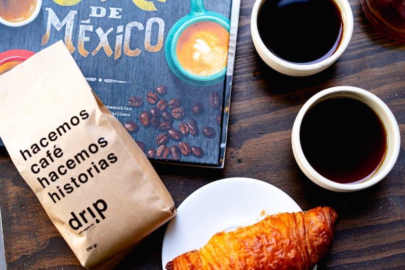 Mexico City Drip Cafe'de iki küçük beyaz fincan sade kahve, beyaz tabakta bir kruvasan ve kahverengi bir kese kağıdı el yapımı kahve