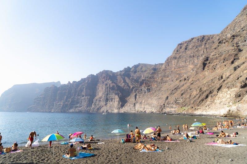 Siyah kumlu volkanik bir plajda turistlerle ve denize bakan devasa kahverengi kayalıklarla Playa los Gigantes sahnesi