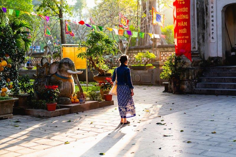Hanoi Vietnam'daki bir Budist tapınağında mavi elbise ve kot ceket giyen kız