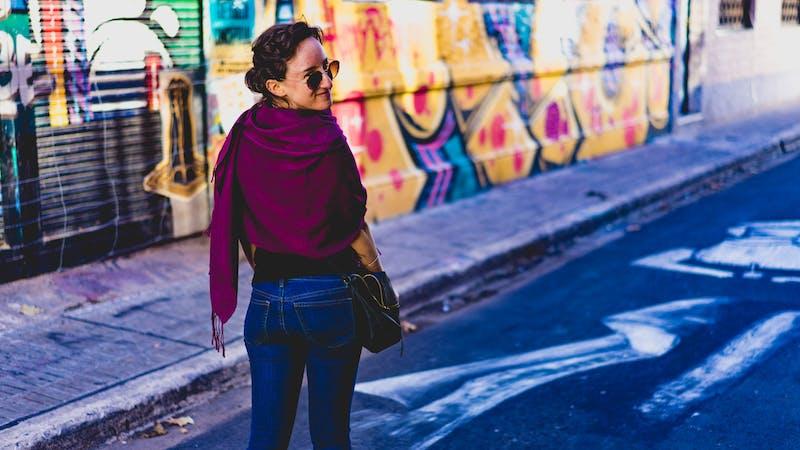 Buenos Aires'te duvar resimleri olan bir yan sokakta yürüyen eflatun bir şal giyen kız