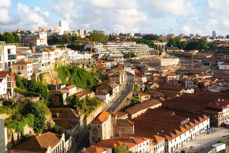 Porto Portekiz'de altın saat, yeşil kayalıklar arasında kırmızı çatılı binaların ve Gaia evlerinin manzarası