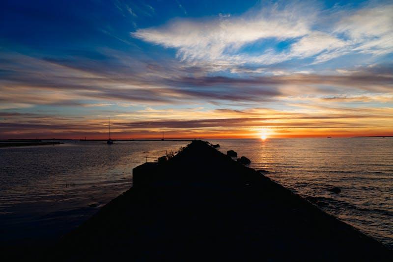 Tallinn Estonya Pirita Plajı'nda güneş batarken, siyah bir kaya iskelesinin gölgesi Baltık Denizi'ne uzanıyor