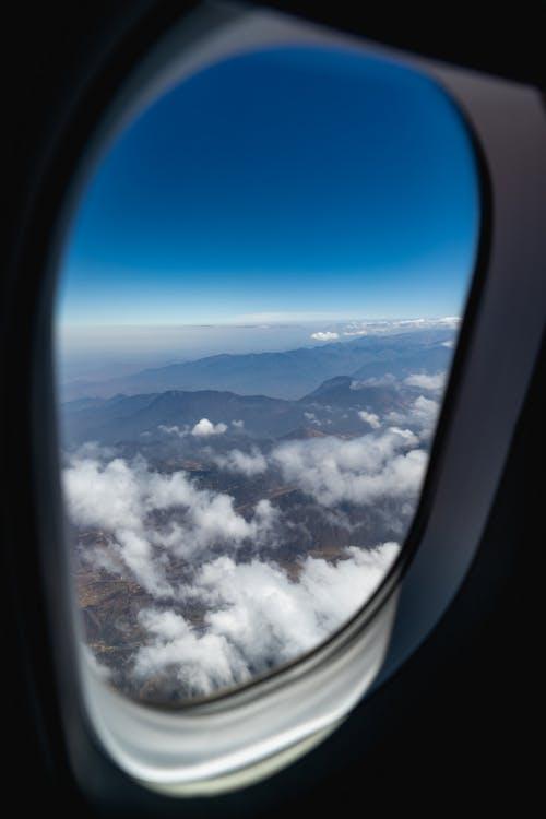 Pürüzlü engebeli dağ silsilesinin uçak penceresi görünümü