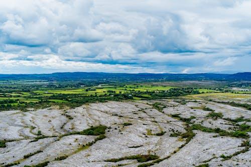 Burren İrlanda mesafesinde parlak yeşil tarım arazileri ve mavi dağlar ile düz kayalık çorak araziler